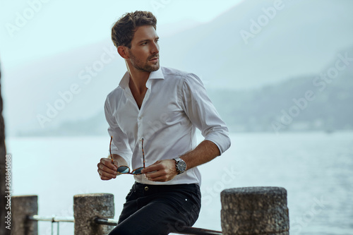 Obraz Stylish man in white classic shirt, looking at the mountains view - fototapety do salonu