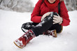 Leinwanddruck Bild - Shot of person during falling in snowy winter park. Woman slip on the icy path, fell, injury knee and sitting in the snow.