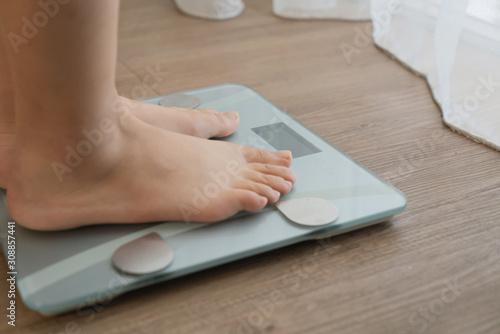 Carta da parati feet on digital weighing scale on wooden floor