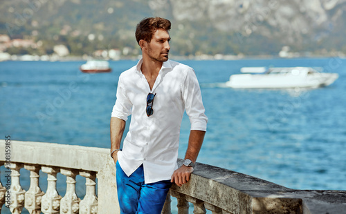 Photo Handsome young man wearing elegant white shirt and posing outdoor near the river