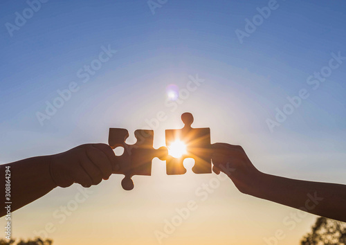 Photo Human hands holding jigsaw puzzle at sunset background