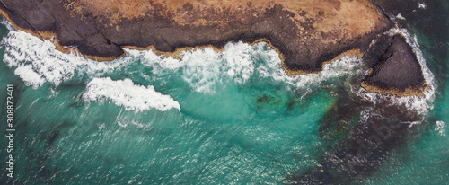 Aerial view of aqua sea waves breaking on rocky cliff, adventure summer travel vacation, perseverance and resilience concept