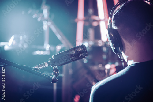 Photo Person with headphones and Studio microphone close-up, in a recording Studio or concert hall, with a drum set