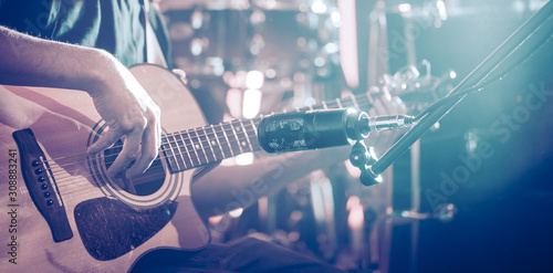 The Studio microphone records an acoustic guitar close-up. Beautiful blurred background of colored lanterns. - 308883241