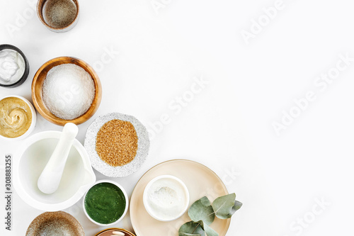 Fototapeta Beauty treatment ingredients for making homemade skin care cosmetic mask. Various bowl with clay, cream, essential oil and natural ingredients  on white table background. Organic spa cosmetic products obraz na płótnie