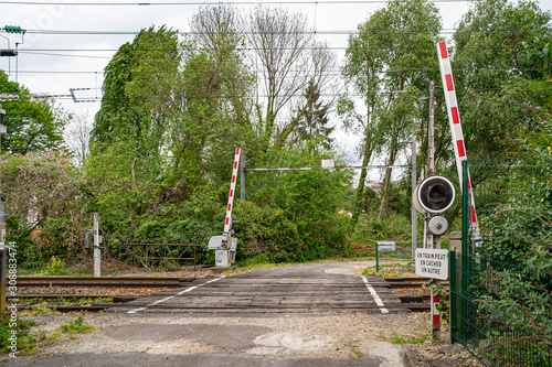 Valokuvatapetti Automatic level crossing on a small road in France, with sign ONE TRAIN MAY HIDE