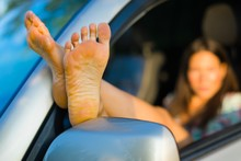 Seductive Woman Having Exposed Bare Feet Out Of Car Window