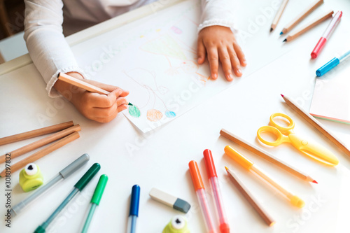 Photo Close up of child's hands drawing at white paper within colorful pens and pencils