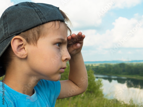 Photo Little boy with untidy bangs in a baseball cap looks out over the horizon