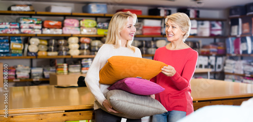 Photo Happy girl and mother enjoying purchased pillows