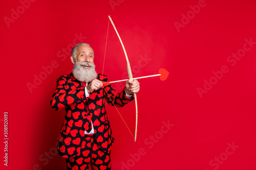 Portrait of his he nice attractive cheery trendy white-haired guy shooting arrows wedding match maker soulmate finding date isolated on bright vivid shine vibrant red color background