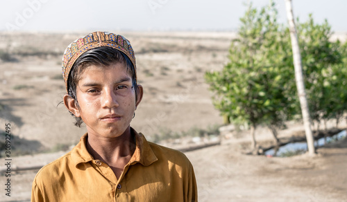 Canvas Print an Afghani homeless boy standing outdoors cause of war and terror
