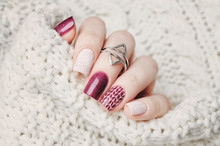 Winter Nail Art Manicure And Knitted Sweater On The Background