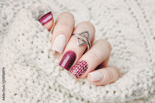 Leinwand Poster winter nail art manicure and knitted sweater on the background