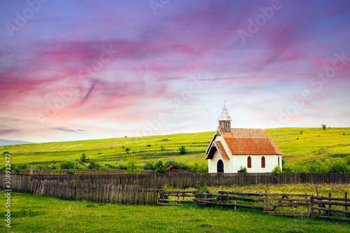 Tablou Canvas Beautiful sunset on a farm with a small catholic church.