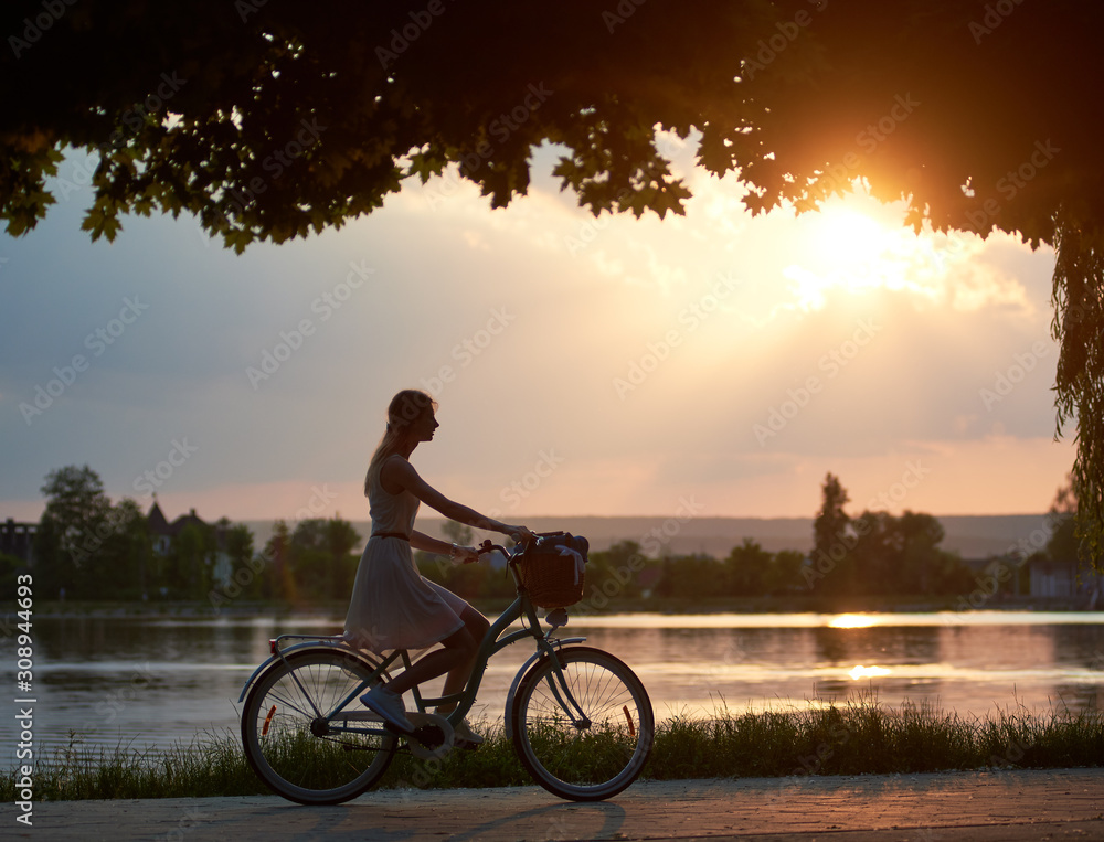 Fototapeta Happy woman riding a retro bike with a basket on the road near the lake on a sunset. Girl enjoying the magical view of the sun's rays of the falling sun at the end of the day
