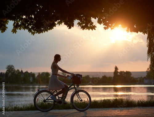 Obraz Happy woman riding a retro bike with a basket on the road near the lake on a sunset. Girl enjoying the magical view of the sun's rays of the falling sun at the end of the day - fototapety do salonu