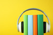 Leinwandbild Motiv Books with modern headphones on yellow background. Space for text