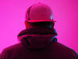 canvas print picture - Neon light man in hoody. Bright colorful light effects. Back view.