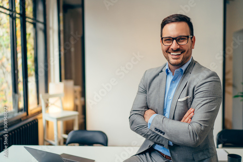 Fotomural Portrait of young businessman standing in his office with arms crossed