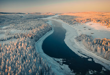 Aerial View Of Frozen River Passing Through Pine Forest