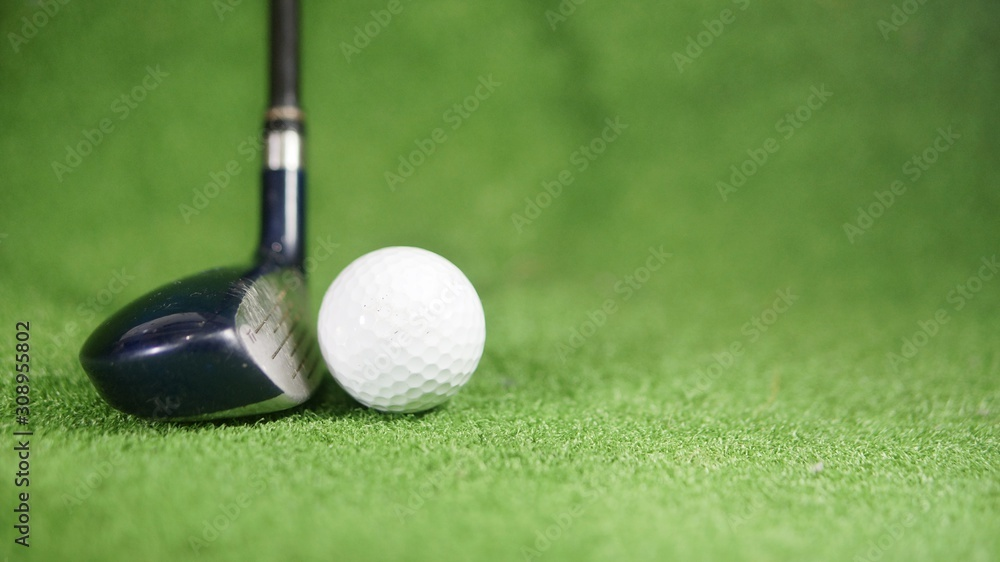 Fototapeta Hybrid golf club and golf ball on green grass