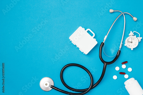 Fototapeta Stethoscope with pills and alarm clock on blue background. Health care and medical examination concept. Top view, flat lay, copy space. obraz na płótnie