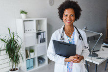 Portrait Of Female African American Doctor Standing In Her Office At Clinic
