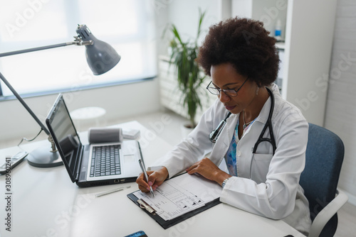 mata magnetyczna Serious concentrated African American doctor working in her office at clinic