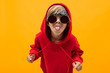 canvas print picture - blond boy with a bandana on his head in a red hoodie with glasses shows his tongue on an orange background