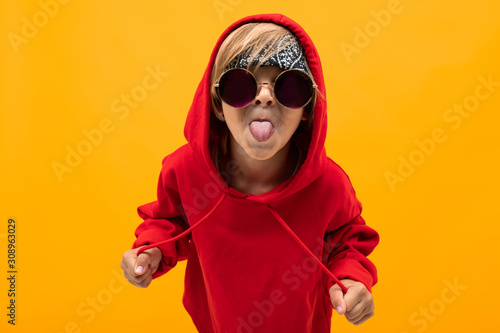 Fotografía  blond boy with a bandana on his head in a red hoodie with glasses shows his tong