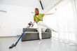Leinwanddruck Bild - Young woman enjoying housework, cleaning floor with cordless vacuum cleaner in the modern white living room. Concept of easy cleaning with a wireless vacuum cleaner