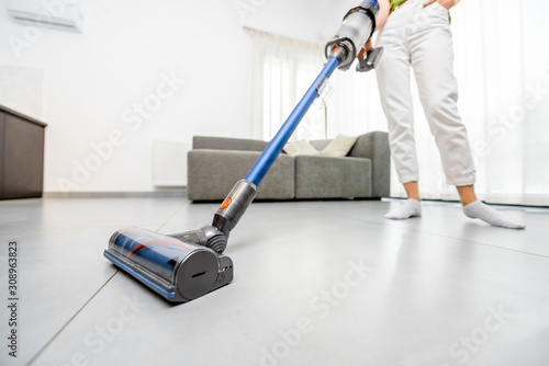 Obraz Woman cleaning floor with cordless vacuum cleaner in the modern white living room. Concept of easy cleaning with a wireless vacuum cleaner - fototapety do salonu