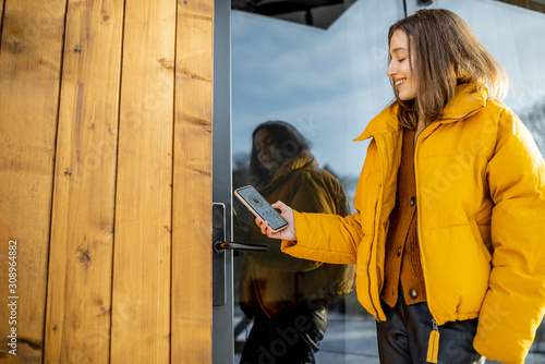 Photo Woman locking smartlock on the entrance door using a smart phone