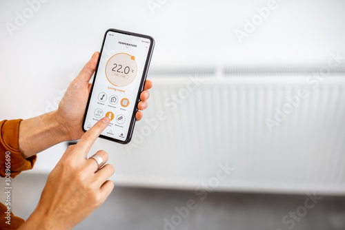 Controlling radiator heating temperature with a smart phone, close-up with radiator on the background. Concept of a smart home and mobile application for managing smart devices at home