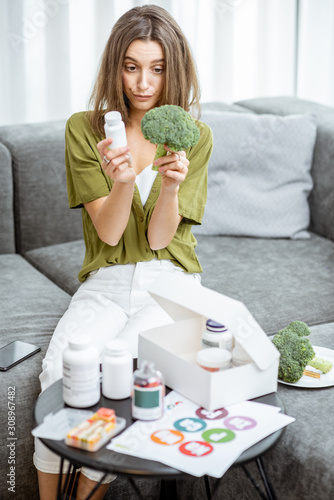 Young woman deciding between nutritional supplements and fresh food while sitting on the couch at home Tapéta, Fotótapéta