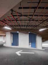 An Arrow Pointing Left In An Underground Parking Garage In Amsterdam, The Netherlands.