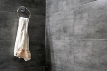 A Light Terry Towel Hangs On A Chromed Ring Holder On A Gray Concrete Wall In The Corner Of A Modern Bathroom