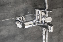Chrome Metal Faucet For Hot And Cold Water, With A Shower Hose, Mounted In A Wall Covered With Gray Tile Imitating Concrete With Water Drops In A Modern Bathroom