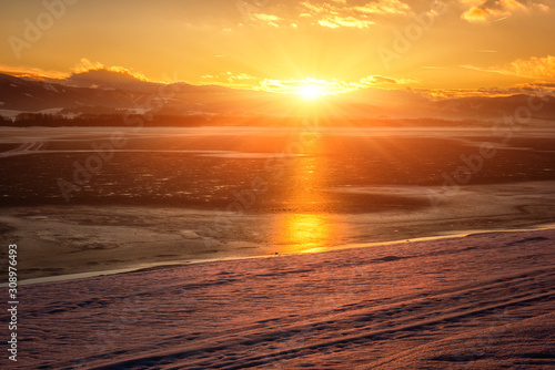Cadres-photo bureau Brun profond Winter golden sunset landscape with lake, snowy bank, mountains on background, sky with clouds and sun. Liptovska Mara, largest water reservoir (dam) in Slovakia (Slovensko), tourist destination