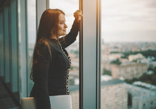 Successful Confident Caucasian Businesswoman Is Dreamily Looking Out The Window With Cityscape Outside While Standing With A Laptop In Her Hand Indoors Of A Top Floor Of A Luxurious Office Skyscraper
