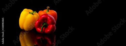 Fotografija yellow, red and orange pepper paprika on a black background, panoramic image