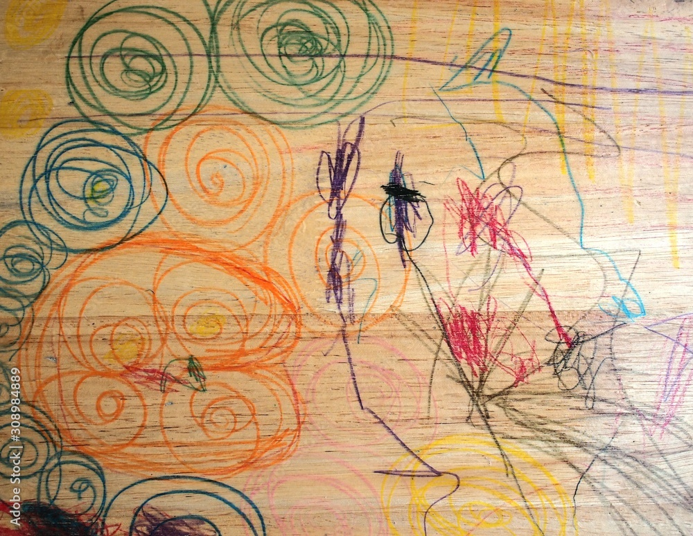 Wooden chair background picture in which a child in a mischievous age uses various colored pens to write in a messy pattern.