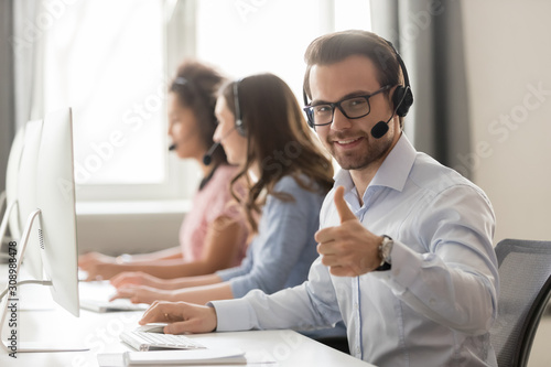 Cuadros en Lienzo  Smiling male employee in headset show thumb up