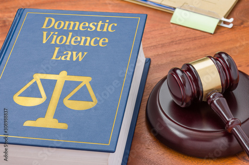 Photo A law book with a gavel - Domestic violence law