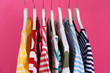 Leinwanddruck Bild - Colorful clothes on hangers against pink background