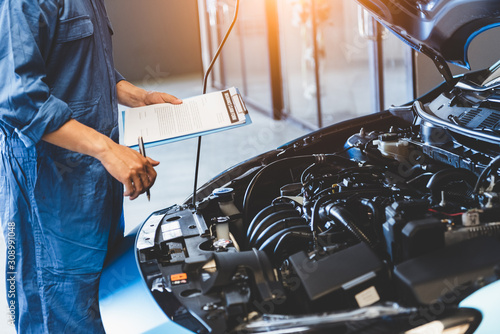 Vászonkép Car mechanic holding clipboard and checking to maintenance vehicle by customer claim order in auto repair shop garage