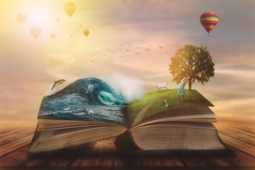 Concept of an open magic book; open pages with water and land and small child. Fantasy, nature or learning concept, with copy space