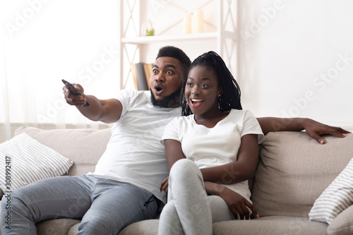 Fototapeta Excited afro couple watching tv together, sitting on couch at home obraz