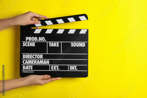 Fotografie, Tablou Woman holding clapperboard on yellow background, closeup with space for text